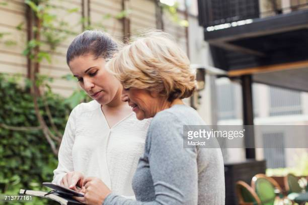 Businesswomen using digital tablet together at office yard