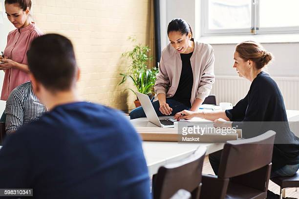 Businesswomen using laptop at table in meeting room