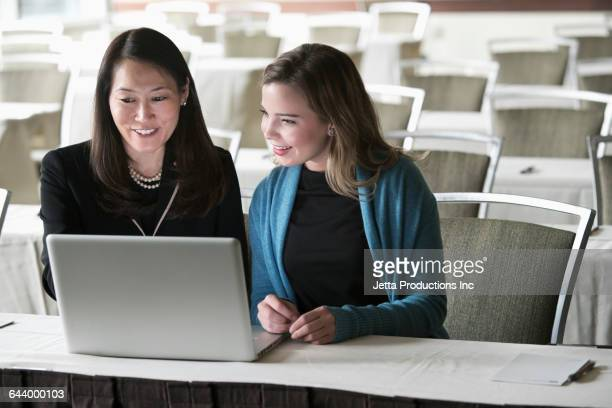Businesswomen using laptop in convention room