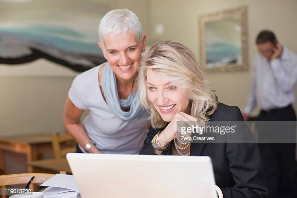 businesswomen using laptop together - 40 49 jaar stockfoto's en -beelden