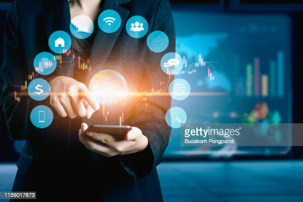 businesswomen using mobile phone analyzing data and economic growth graph chart. technology digital marketing and network connection. - information medium stock pictures, royalty-free photos & images
