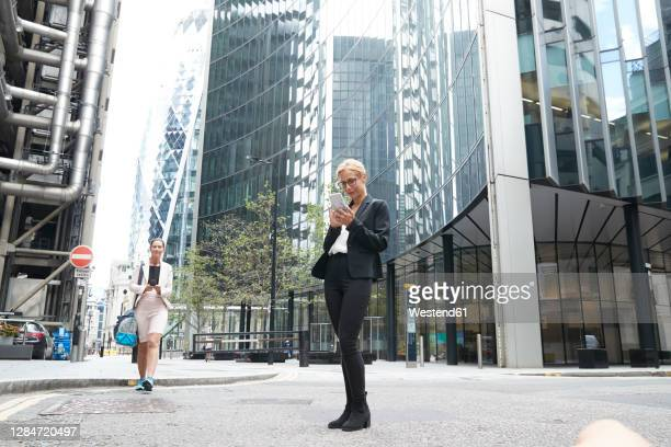 businesswomen using smart phones against office buildings at downtown - entrepreneur stock pictures, royalty-free photos & images