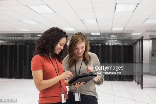 Businesswomen using tablet computer in server room