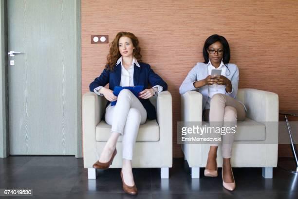 mujeres empresarias a la espera de una entrevista de trabajo - piernas cruzadas fotografías e imágenes de stock
