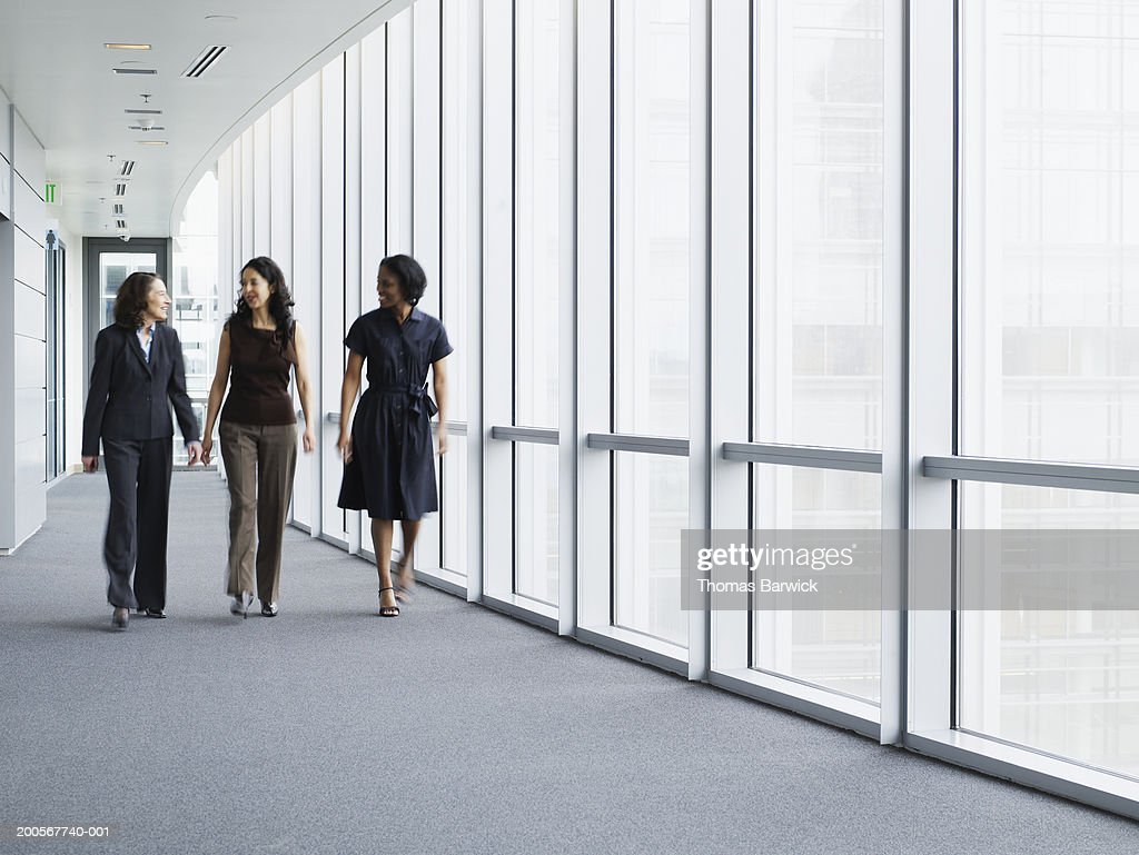 Businesswomen walking in hallway, smiling, portrait : Stock Photo