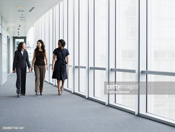 businesswomen walking in hallway, smiling, portrait - overheid stockfoto's en -beelden