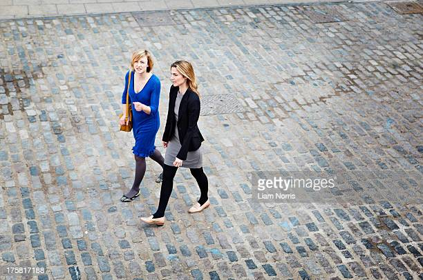 Businesswomen walking on cobbled street, high angle