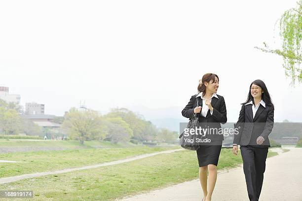 Businesswomen walking the riverbed