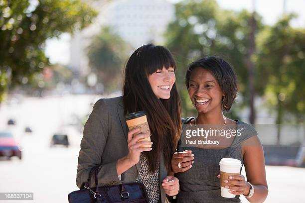 businesswomen walking together outdoors - lunch break stock photos and pictures