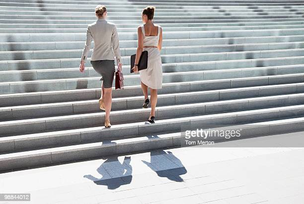 businesswomen walking up steps outdoors - stairs stock photos and pictures