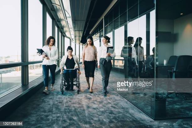 businesswomen walking with disabled female entrepreneur in corridor at workplace - disability stock pictures, royalty-free photos & images