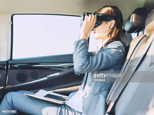 businesswomen wearing VR glasses in car