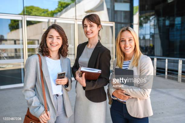 businesswomen with books and smart phone smiling at camera - shoulder bag stock pictures, royalty-free photos & images