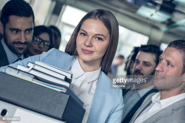 Businesswomen with hands full of documents leaving elevator