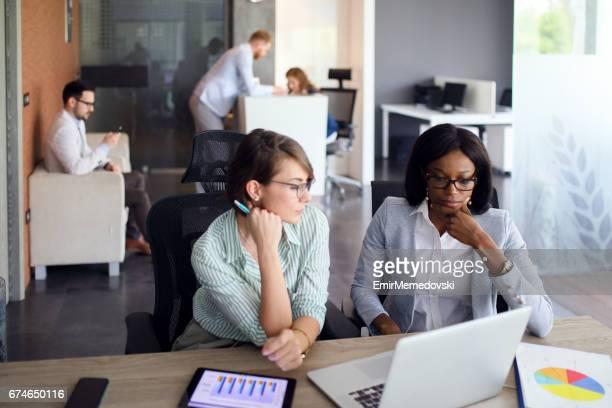 Femmes d'affaires avec ordinateur portable, tablette numérique et papier graphique coopérant