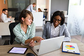 Businesswomen with laptop, digital tablet and chart papers cooperating