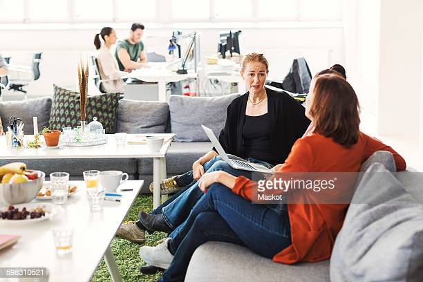 Businesswomen with laptop discussing project on sofa in office lobby