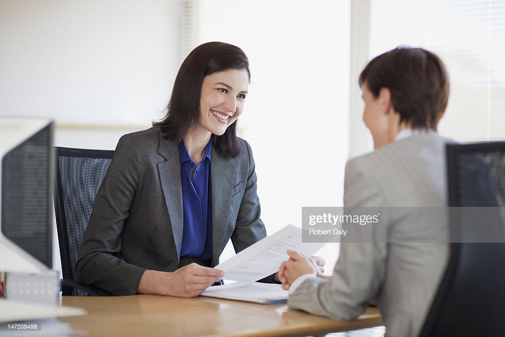 Businesswomen with paperwork talking face to face : Stock Photo
