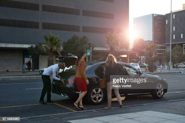 Businesswomen with rolling suitcases getting into a cab, at sunset