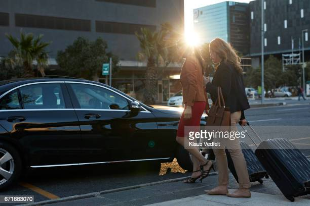 Businesswomen with rolling suitcases hailing a cab