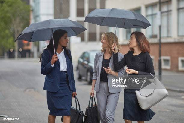 Businesswomen with umbrellas talking on street
