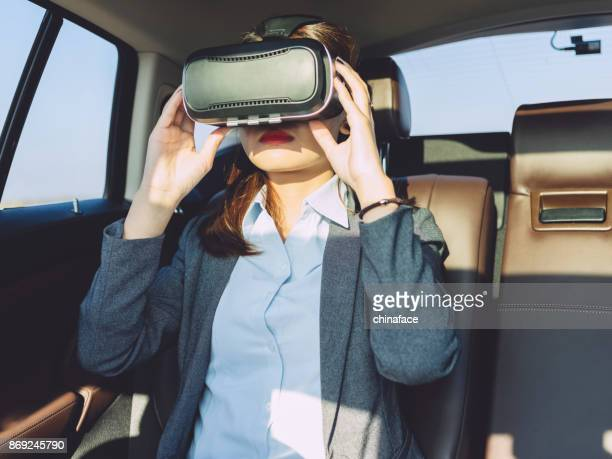 businesswomen with VR glasses in car