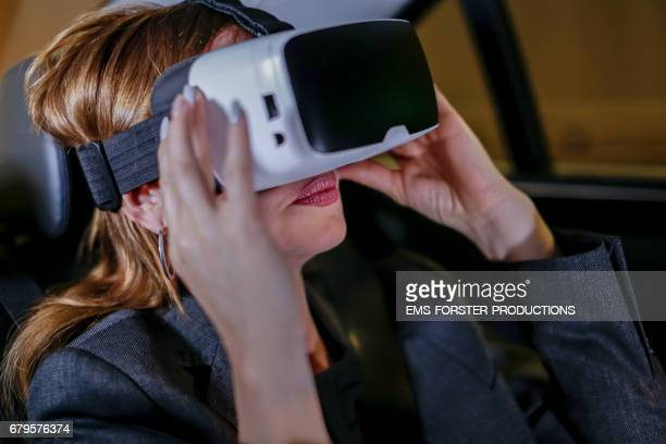 businesswomen with VR glasses in car / taxi