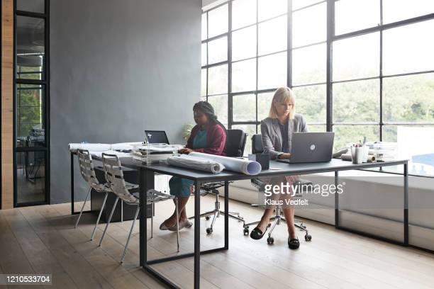 businesswomen working at desk in office - differing abilities female business fotografías e imágenes de stock