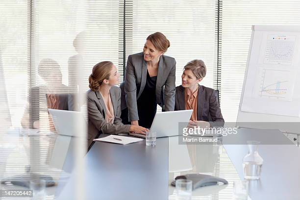 Businesswomen working at laptop in conference room