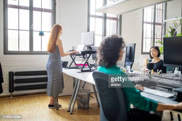 businesswomen working at modern office space - ergonomics stock photos and pictures