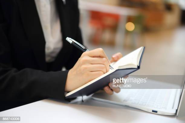 businesswomen working on document at desk - handbook stock photos and pictures