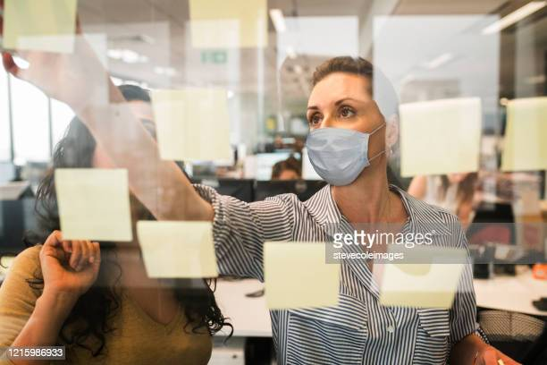 businesswomen working together behind glass wall with reflections wearing mask. - coronavirus australia stock pictures, royalty-free photos & images