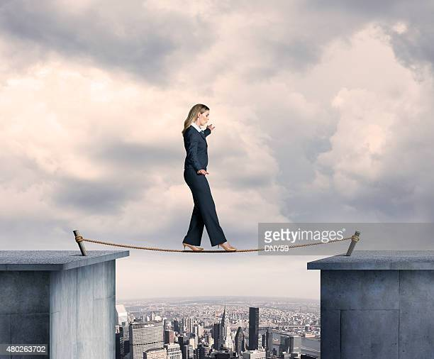 Busineswosman Balancing On A Tightrope Above Big City