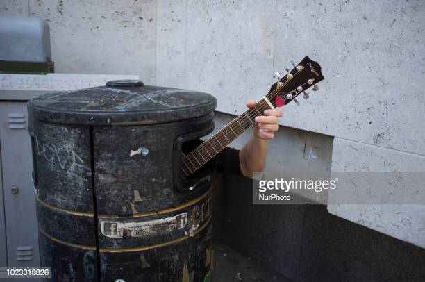 A busker is pictured as he plays guitar into a garbage bin in Cambridge on August 25 2018 Cambridge is home to the worldrenowned University of...