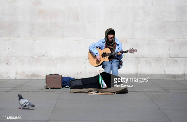 A busker is seen on his own outside the National Gallery in Trafalgar Square on March 21 2020 in London England Coronavirus has spread to at least...