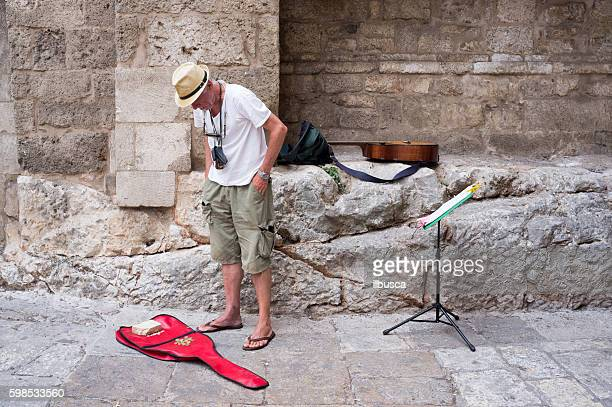 Busker looking at coins on his guitar case in Ostuni
