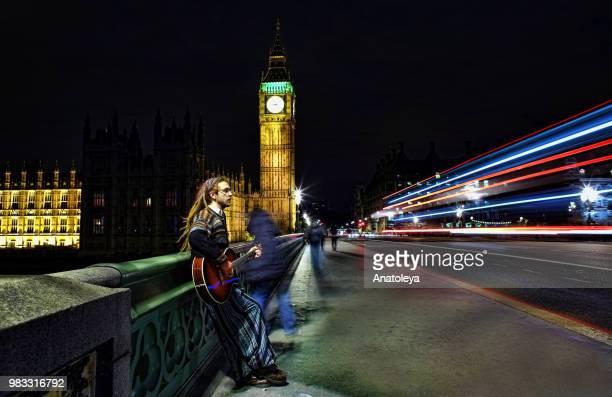 Busker on Westminster Bridge at night