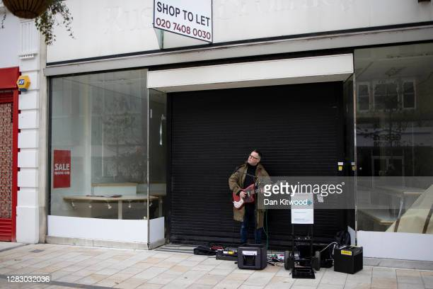 Busker outside a closed down shop on Bromley High Street on October 30, 2020 in Bromley, England. With lockdowns creeping across the country as...