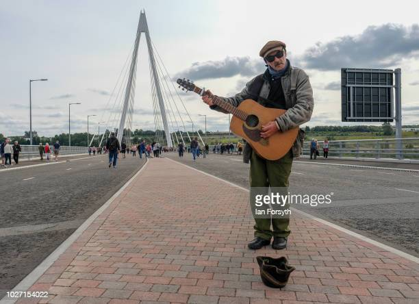 A busker performs as members of the public cross the new Northern Spire bridge spanning the River Wear as it opens for a pedestrian walkover on...