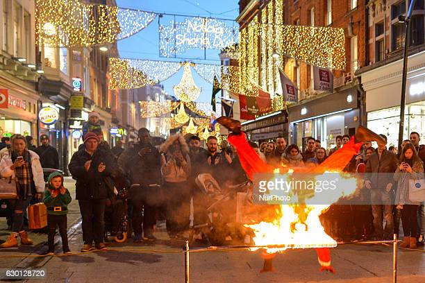 A busker performs his act dressed as Sainta on Dublin Grafton Street decorated and lit for the Christmas season On Friday 16 December 2016 in Dublin...