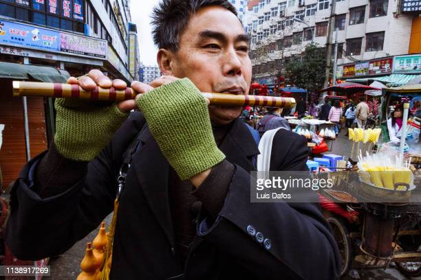 busker playing a bamboo flute in chengdu - bamboo flute stock photos and pictures