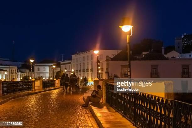 busker tocando un acordeón de piano por la noche en roman bridge en tavira, portugal - faro city portugal fotografías e imágenes de stock