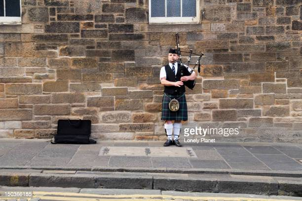 Busker playing bagpipes outside Edinburgh Castle.