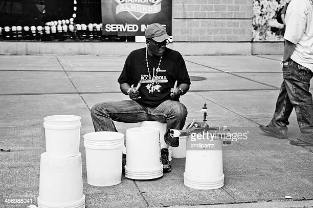 busker playing plastic buckets - drum container stock photos and pictures