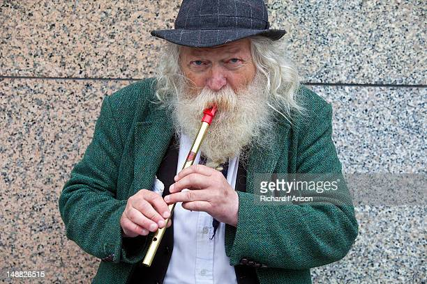 Busker playing tin whistle on O'Connell Street.