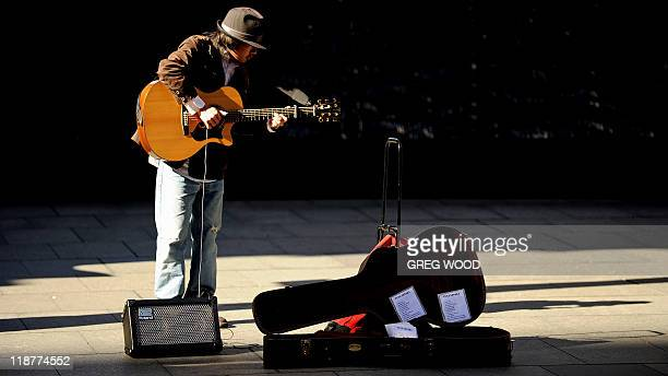 A busker plays a guitar as he stands in a narrow strip of sunshine in central Sydney on July 11 2011 during a respite from icy conditions A cold snap...