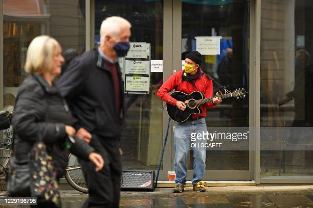 Busker plays a guitar while wearing a face mask or covering due to the COVID-19 pandemic, in the shopping district in central Sheffield, south...