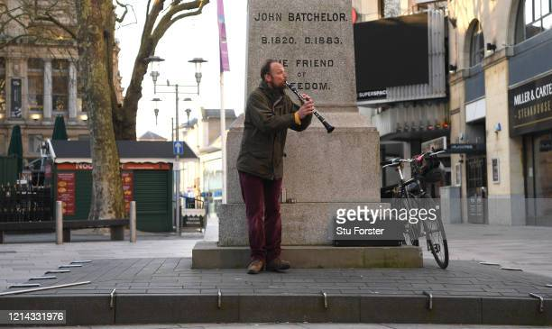 A busker plays his clarinet to an empty street during eveving rush hour in Cardiff City centre on March 23 2020 in Cardiff Wales Coronavirus pandemic...