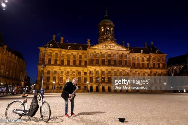 Busker plays in front of the Koninklijk Paleis or The Royal Palace Amsterdam , which is closed to the public until further notice on April 04, 2020...