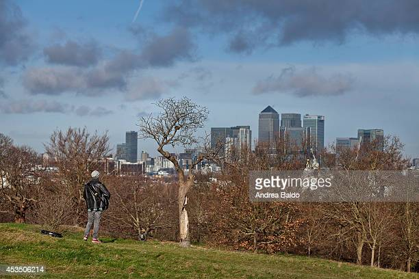 A busker plays in Greenwich Park On the background Canary Wharf